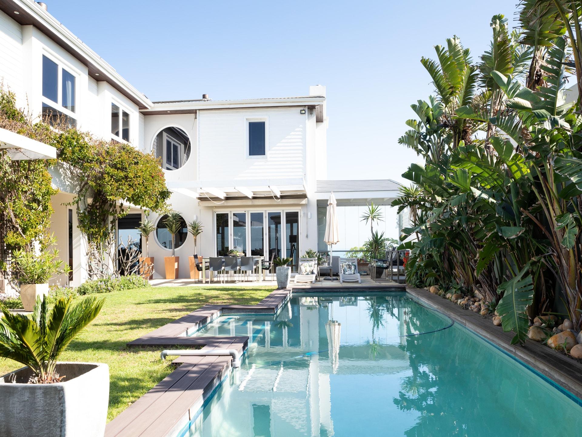 outdoor living swimming pool white retro house lush green garden
