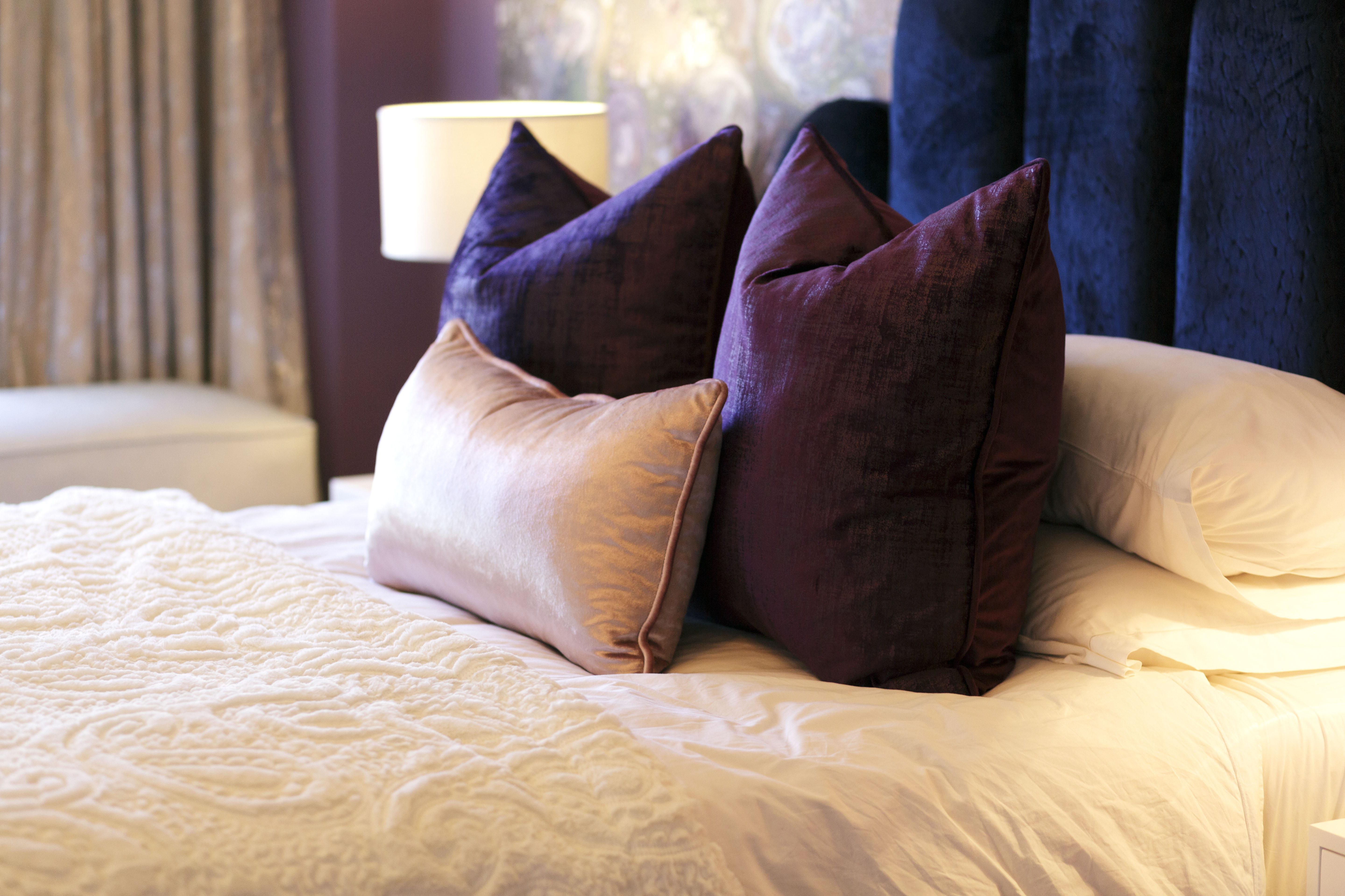 bed with pink and purple velvet and satin scatter cusions in a crystal gemstone bedroom